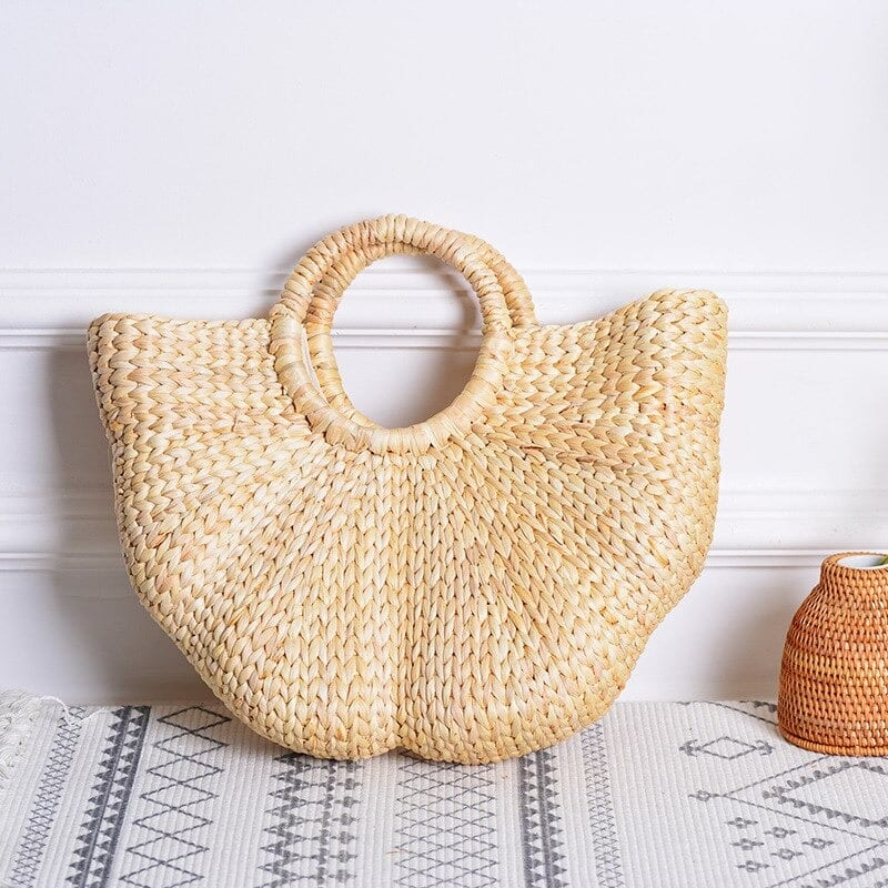 Knitted straw bag with leather handles suggest